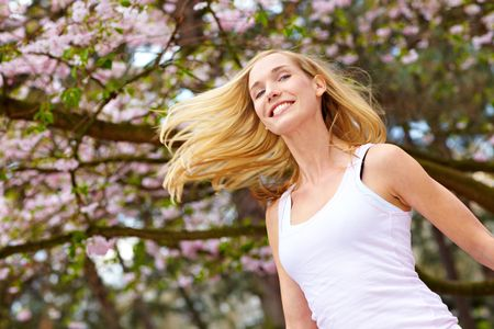 Young woman jumping under a blooming cherry tree photo