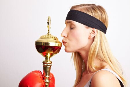 Young female boxer with red boxing gloves kissing a trophy photo