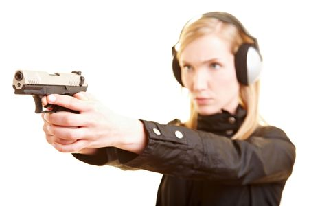 studio shoot: Young female shooter with pistol and ear protection