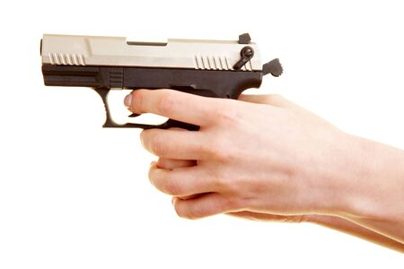 Two female hands holding a pistol ready to shoot photo