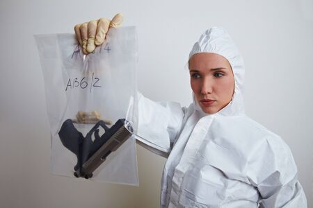Female forensic scientist holding weapon and ammunition Stock Photo - 6860499