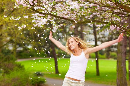 location shot: Young woman under a blooming cherry tree Stock Photo