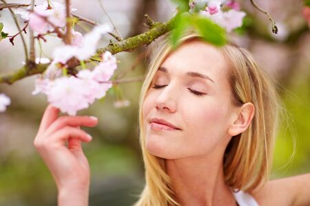 location shot: Young woman smelling the blossoms on a cherry tree