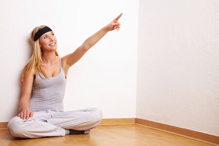 tailor seat: Young woman sitting on the floor in a fitness center Stock Photo