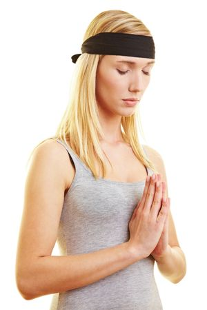 hoping: Young woman with headband folding her hands Stock Photo