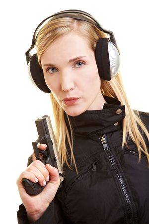 Young female shooter with pistol and ear protection photo