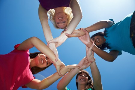 grasp: Four female friends holding each other on the wrists Stock Photo