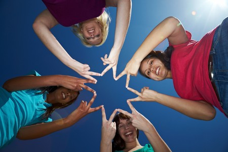 Four women forming a star shape with their fingers Stock Photo - 7222639