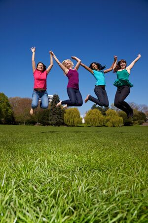 Four happy young women jumping into the air Stock Photo - 7222641