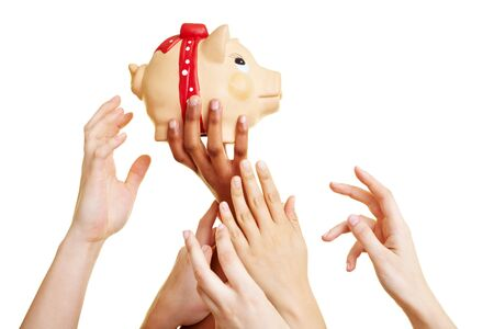 Many desperate hands reaching for a piggy bank photo