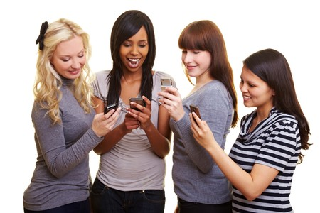 mobilephones: Four young women reading text messages on their cell phones Stock Photo