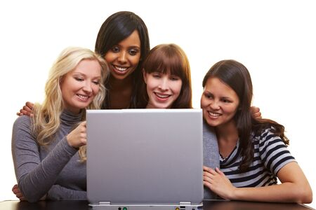 Four young happy woman centered around a laptop Stock Photo - 7222629