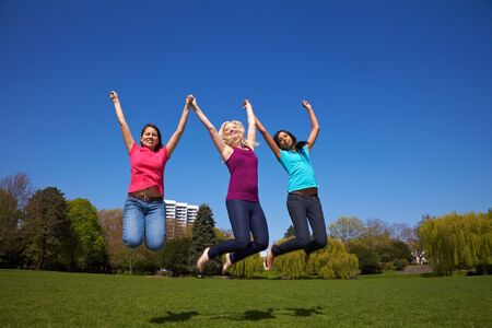 Three happy young woman jumping in a park Stock Photo - 7222642