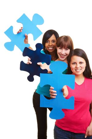 Three young happy women holding big jigsaw pieces Stock Photo