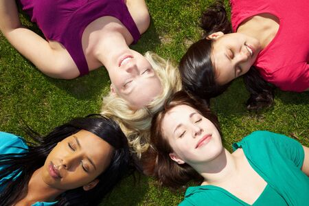 woman back of head: Four young women sunbathing in a park with eyes closed Stock Photo