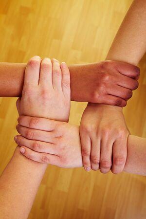 solidaridad: Cuatro manos sosteniendo entre s� en las mu�ecas  Foto de archivo