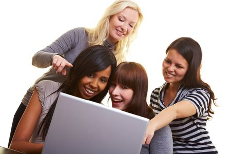 centered: Four young happy woman centered around a laptop Stock Photo