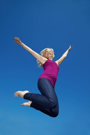 Happy young woman jumping into the air Stock Photo - 7222653