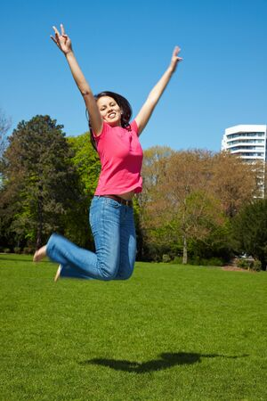 young happy asian woman jumps into the air photo