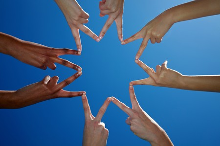 Eight hands form a star with their fingers photo