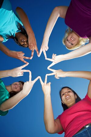 Four women forming a star shape with their fingers photo