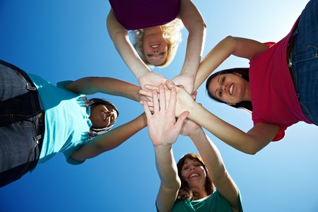 Four young women stacking their hands on top of each other Stock Photo - 7230617