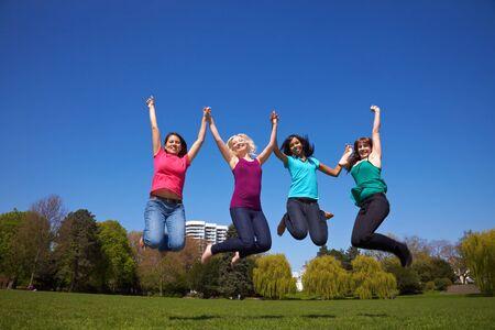 Cuatro mujeres jóvenes felices saltando en el aire  Foto de archivo