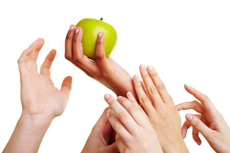 Many desperate hands reaching for a green apple Stock Photo - 7230586