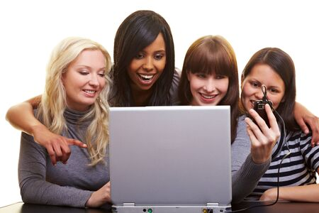 Four young happy woman centered around a laptop photo