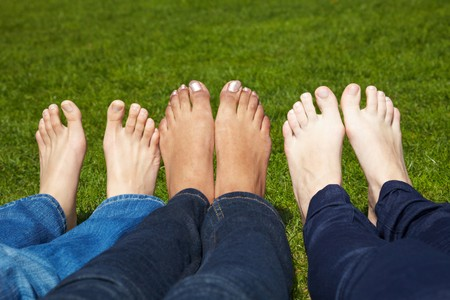 Three women with naked feet lying in grass photo