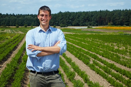 location shot: Happy farmer with arms crossed in front of his fields