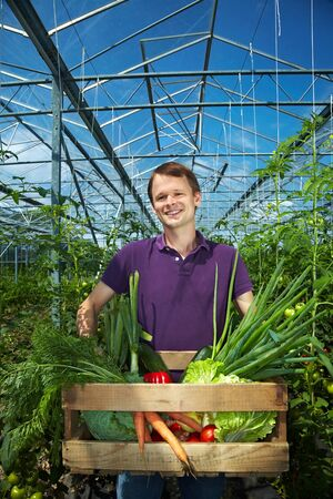 Happy farmer with vegetable box in a greenhouse photo
