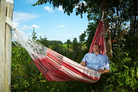 location shot: Young man taking a break in a hammock