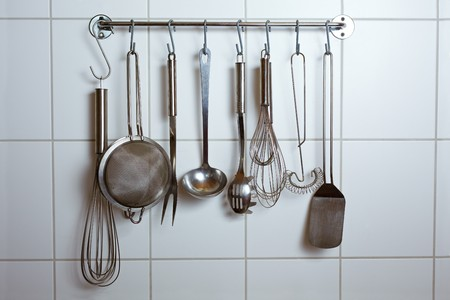 kitchen tool: Many different kitchen tools on hooks in a kitchen Stock Photo