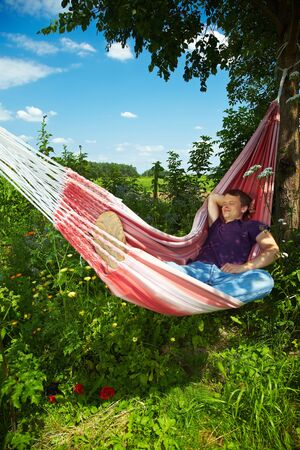 lean back: Young man sleeping relaxed in his hammock