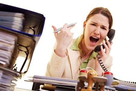 insult: Businesswoman sitting at her desk and screaming into a phone