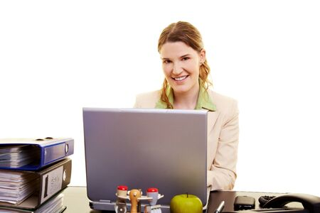 electronically: Smiling woman sitting at her desk with a laptop