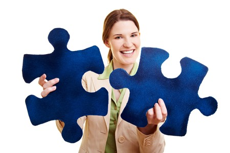 Happy businesswoman holding two oversized jigsaw pieces photo