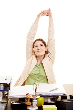 student desk: Happy businesswoman stretching her arms at her desk Stock Photo
