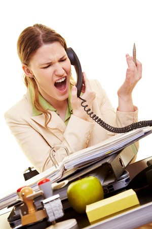 Businesswoman sitting at her desk and screaming into a phone photo
