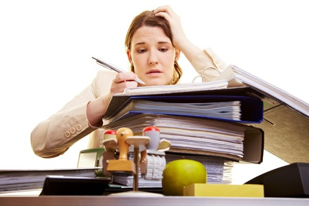 hectic: Businesswoman with pen reading in files on her desk