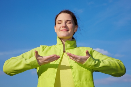 hands in the air: Young woman doing some breathing exercises outdoors