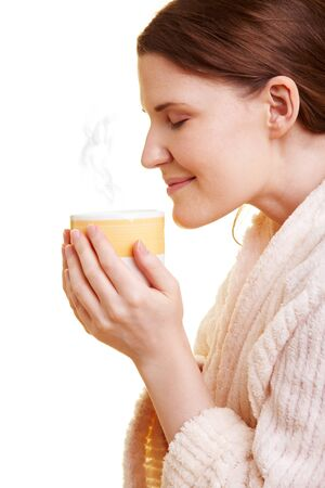 sense of space: Happy woman in bathrobe smelling her cup of coffee
