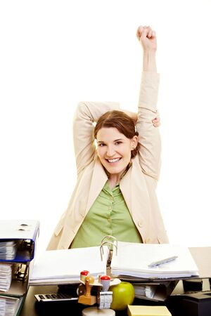 Happy businesswoman stretching her arms at her desk photo