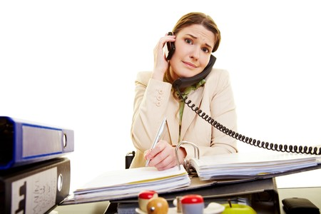 office chaos: Young businesswoman on two phones taking notes Stock Photo