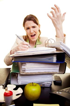 Angry businesswoman with pen reading in files on her desk photo