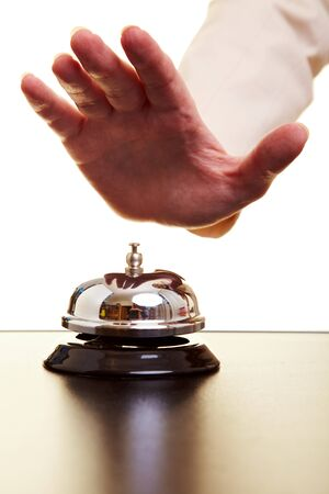 hotel service: Hand of a businesswoman using a hotel bell