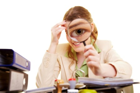 scepticism: Businesswoman at desk looking through magnifying glass