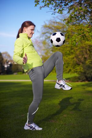 Young woman playing with a soccer ball in a park photo