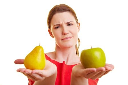 梨: 若い女性がりんごとナシを比較します。